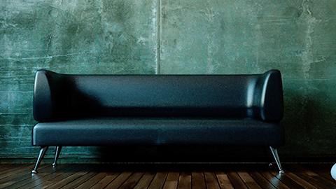 Ein leeres schwarzes Ledersofa steht vor einer kahlen Betonwand. (Link zu Informationen über Missbrauch in der Therapie)