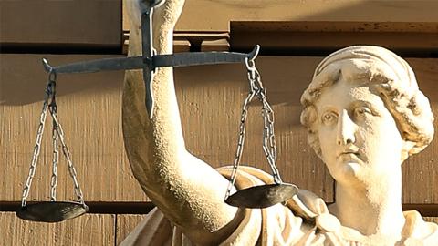 Statue einer Justitia mit Waage. (Link zu: Psychosoziale Prozessbegleitung)