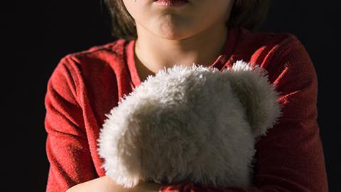 Trauriges Kind hält Teddy fest im Arm. (Link zu Informationen über Sexuellen Missbrauch)