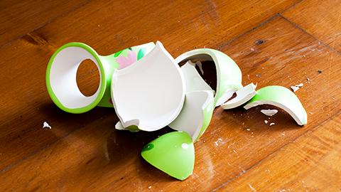 Eine Vase liegt zebrochen auf Dielenfußboden. (Link zu Informationen über Häusliche Gewalt)