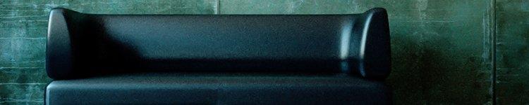 Ein leeres schwarzes Ledersofa steht vor einer kahlen Betonwand.