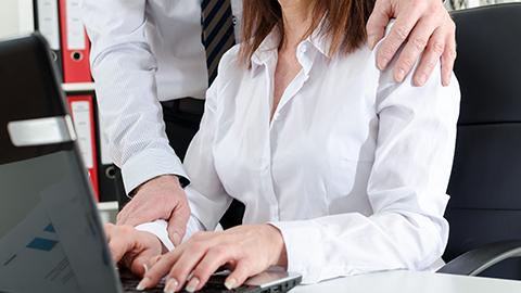 Kollege legt Frau ungewollt die Hand um die Schulter. (Link zu Informationen über Sexuelle Belästigung am Arbeitsplatz)
