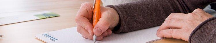 Eine Hand schreibt etwas mit einem orangenen Kugelschreiber auf einen Block.